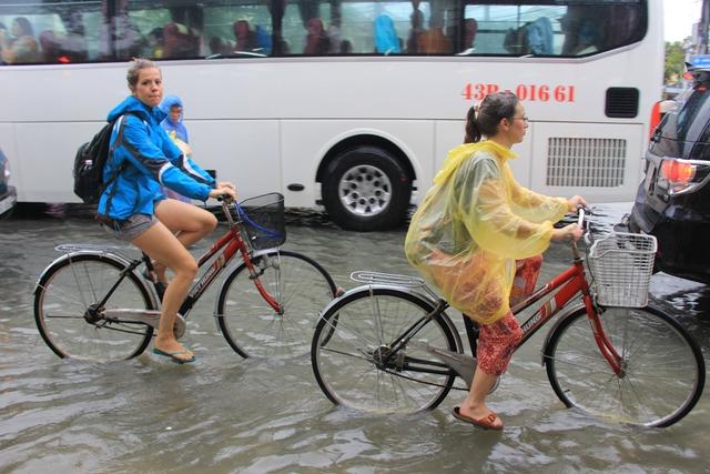 ...một số khách du lịch thuê xe đạp đạp trong nước lũ để trải nghiệm với cảm giác thú vị