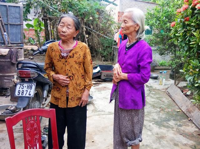 Bà Phạm Thì Duyền (áo tím) và bà Nguyễn Thị Quyên ghé tai nhau kể lại việc bị thôn bớt quà cứu trợ. Ảnh: M.K