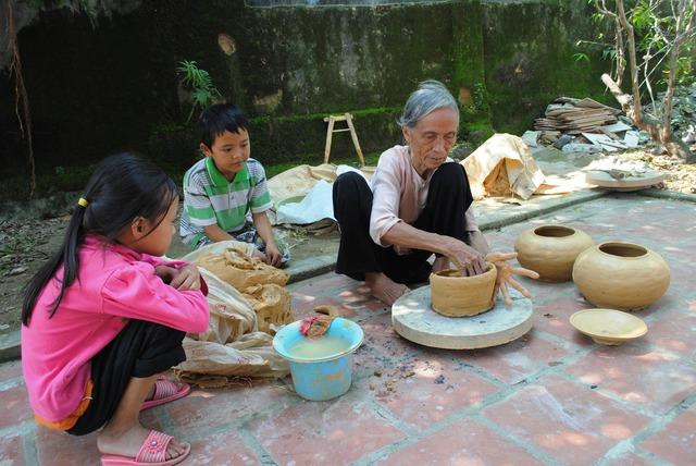 Những đứa trẻ chăm chú học nghề làm nồi đất.