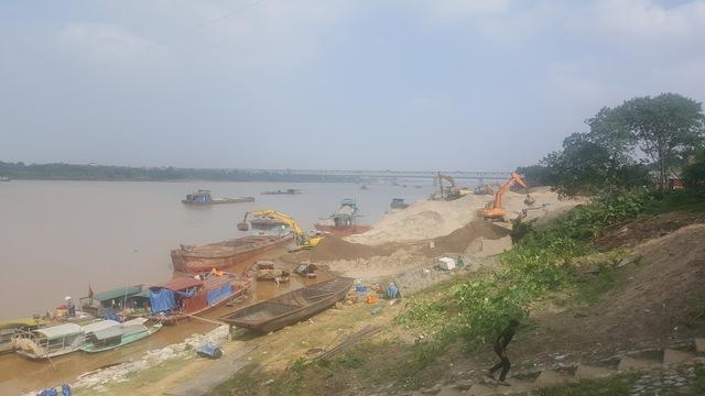 Một bãi tập kết cát ngay cạnh chân cầu Thăng Long. Ảnh: T.G