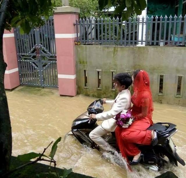 Chú rể chở cô dâu trên xe máy đi trong nước lũ. Ảnh: Facebook