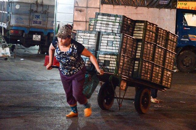 Nửa đêm về sáng, chợ hoa quả ở chân cầu Long Biên vào thời điểm nhộn nhịp nhất. Ở đây tập trung rất nhiều lao động nữ, công việc chủ yếu của họ là kéo xe và gánh hàng thuê cho các lái buôn hoa quả. Trong ảnh là chị Lương, 48 tuổi, quê Thanh Hóa đang gồng mình kéo chiếc xe hàng có trọng lượng nặng gấp vài lần cơ thể mình.