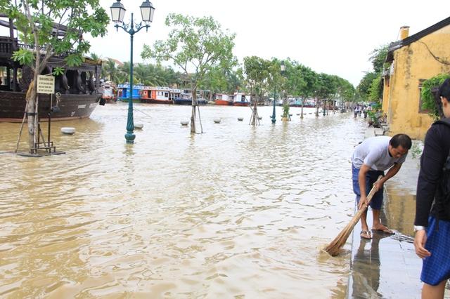 Đến chiều 3/11, nước lũ bắt đầu rút dần trên đường Bạch Đằng, người dân tranh thủ vừa bán hàng, vừa quét dọn nhà cửa...