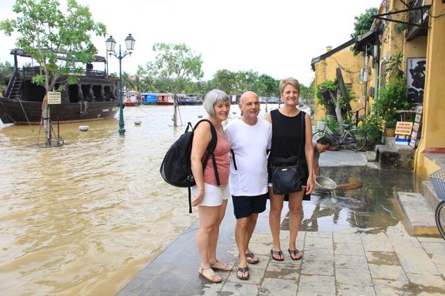 Ba du khách nước ngoài lưu lại hình ảnh bên nước lũ trên đường Bạch Đằng làm kỷ niệm trong hành trình khám phá phố cổ