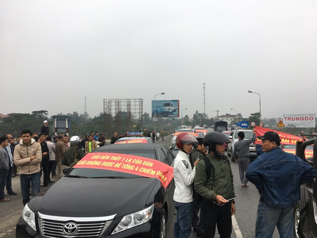 Người dân mang xe cùng với băng rôn chặn đường phản đối trạm thu phí