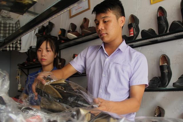 Tài cẩn thận kiểm tra các mẫu hàng tại cửa hàng trước khi giao cho khách hàng