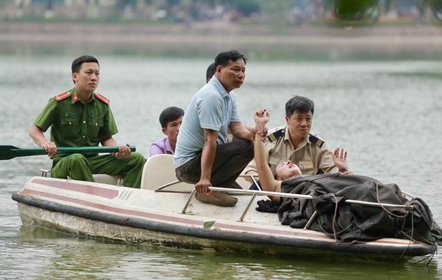 Lực lượng chức năng dùng thuyền vớt nữ du khách đưa vào bờ. Ảnh: Tuấn Đào.