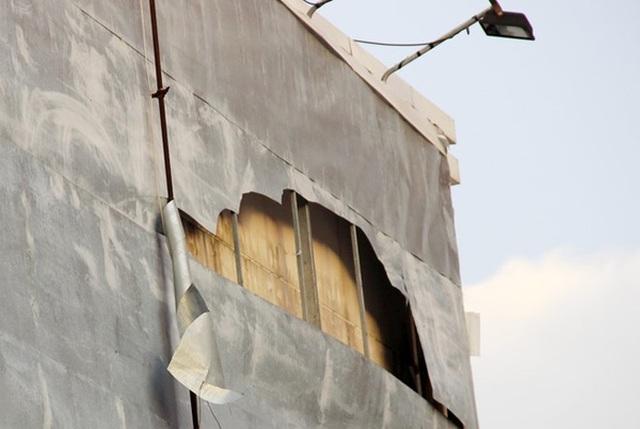 Vẫn còn nhiều tấm tôn hư hỏng trên biển quảng cáo cũ của cửa hàng viễn thông sắp rơi xuống. Nếu gió giật mạnh những tấm tôn này có thể sẽ bay ra đường gây nguy hiểm cho nhiều người. Ảnh: Việt Tường.