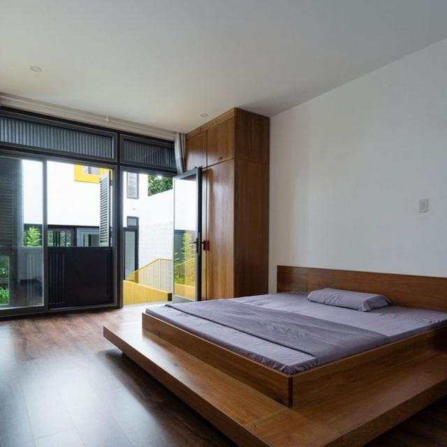 Phòng ngủ siêu tối giản với giường lớn và tủ quần áo cao sát trần. Nhờ nhà được chia khối mà không gian nào cũng rất thoáng và sáng.