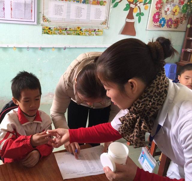 Học sinh trường Tiểu học xã Hạ Bì (Kim Bôi, Hòa Bình) được uống thuốc tẩy giun. Ảnh chụp sáng 29/11. Ảnh: V.Thu