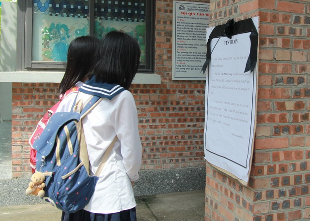 Học sinh tại trường THCS - THPT Lương Thế Vinh, cơ sở Tân Triều đọc Tin buồn dán trước cổng trường về thông tin lễ viếng của người thầy đáng kính, PGS.TS Văn Như Cương.