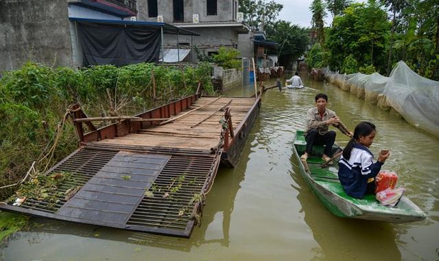 Một tuần người dân phải đi lại bằng thuyền sau sự cố vỡ đê Bùi 2.     ảnh: H.P
