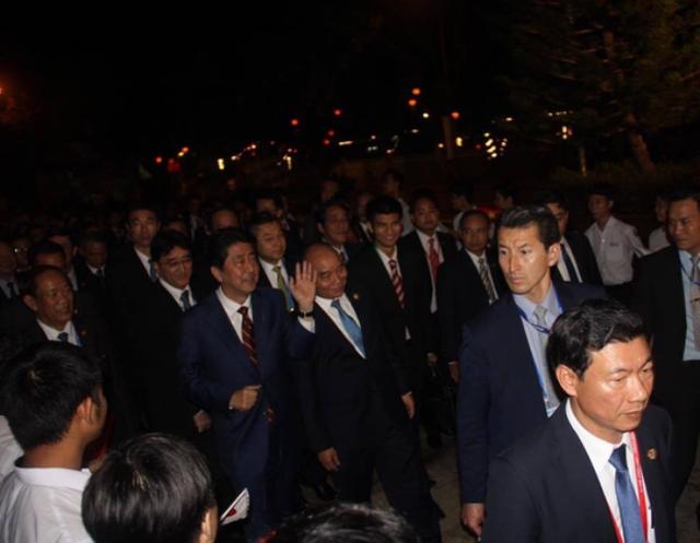 Thủ tướng Abe vẫy tay chào người dân khi cùng đi bộ ở phố cổ Hội An cùng Thủ tướng Nguyễn Xuân Phúc tối 11-11