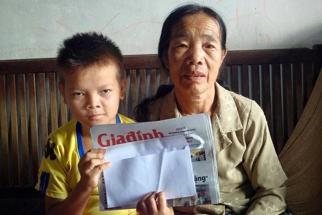 Hiếu và bà ngoại nhận quà từ quỹ Vòng tay Nhân ái. Ảnh: H.Phương