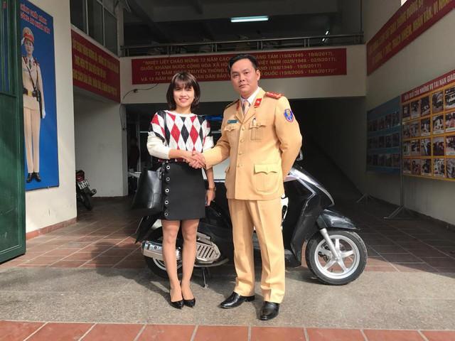 Đại úy Nguyễn Tuấn Cường trao trả chiếc xe bị đánh cắp cho chị Nguyễn Thị Hương