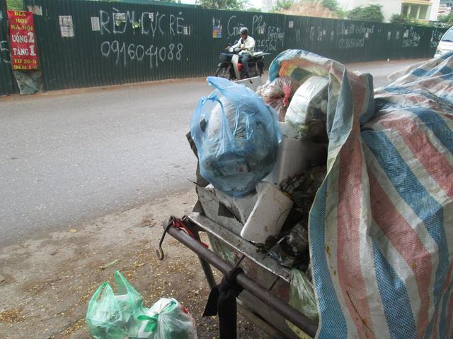 Những xe, túi rác la liệt bên đường ở phường Định Công vào sáng 25/7. Hà Nội đang có mưa nhiều nên những vật tuy nhỏ như hũ sữa chua, hộp sữa, túi ni-lon... tụ nước đều có thể trở thành cơ hội cho muỗi vằn sẽ sinh sôi.