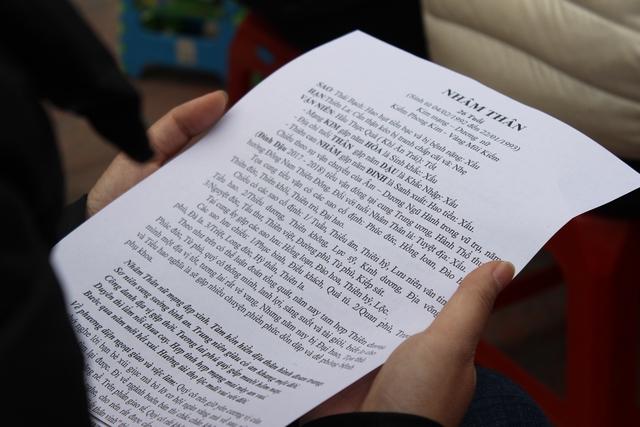Nhiều người tranh thủ thời gian trước giờ lễ mở sách khấn để đọc.