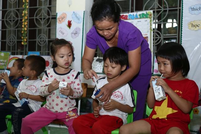 ô giáo tại trường tiểu học mầm non Châu Cường – Huyện Quỳ Hợp đang hướng dẫn và giúp các em cách cho ống hút sữa để uống sữa