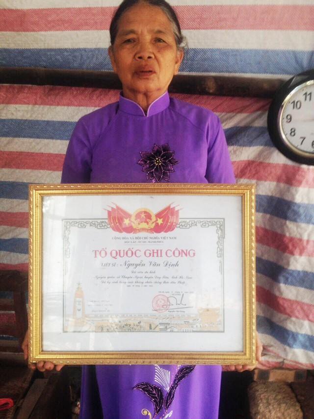 Bà Nguyễn Thị Lụa và tấm bằng Tổ Quốc ghi công dành cho liệt sĩ Nguyễn Văn Định - bố của bà.