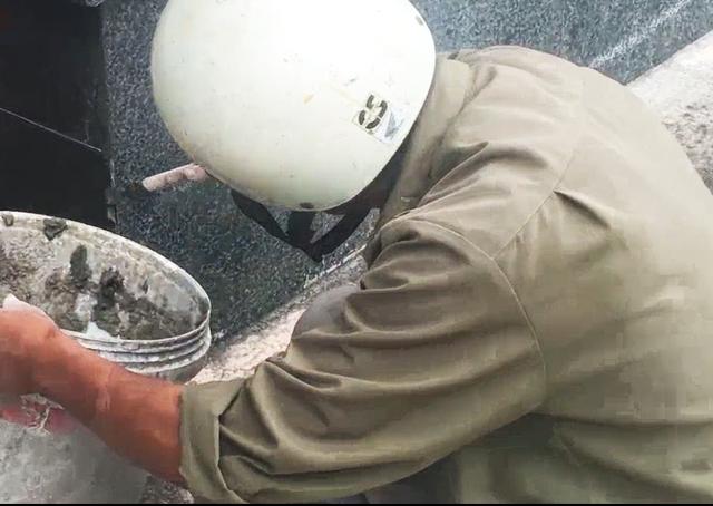 Công nhân đội mũ bảo hiểm, dùng que tre bôi xi măng vào các kẽ hở trên mạch đá