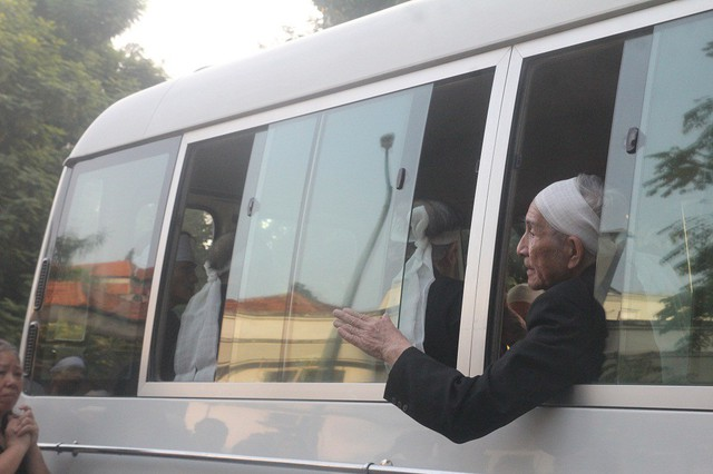 Con trai cả vẫy tay gửi lời chào cuối cùng với mọi người trước khi đưa mẹ của ông về nơi an nghỉ cuối cùng.