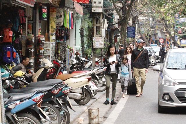 Người đi bộ lại bị đẩy xuống lòng đường khi lực lượng chức năng rút đi (ảnh chụp tại phố Mã Mây lúc 12h30' ngày 10/3). Ảnh: H.P