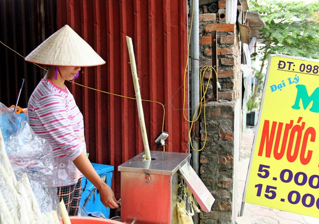 Chị Xuyên luôn phải làm luôn chân luôn tay để phục vụ nước mía cho khách hàng. Ảnh:k.O