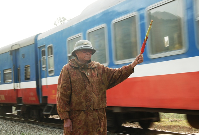 Ông Nguyễn Huy Chi hàng ngày đứng canh trên đường ngang dân sinh.