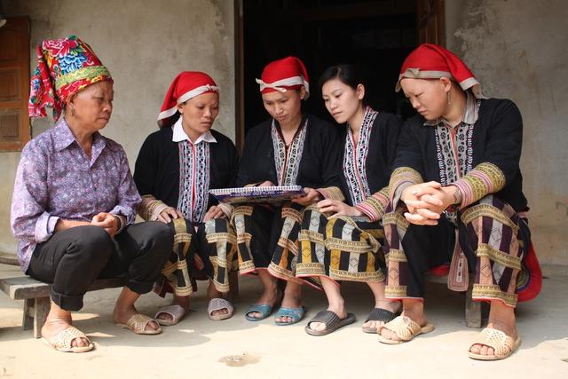 Cán bộ chuyên trách dân số, y tế thôn bản (giữa) tuyên truyền cho người dân Phìn Ngan (Bát Xát, Lào Cai) về thực hiện chính sách DS-KHHGĐ. Ảnh: Hồng Tấm