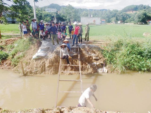 Người dân bò, ngồi chệt để trườn qua cây cầu tạm làm bằng thang sắt. Ảnh: N.Hưng