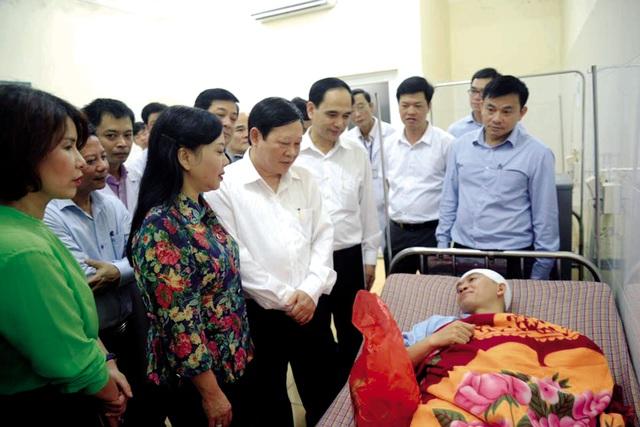 Bộ trưởng Nguyễn Thị Kim Tiến thăm hỏi, động viên BS Lê Quang Dương (BVĐK Thạch Thất) – người bị bố bệnh nhi cầm cốc ném vào đầu. ảnh: T.G
