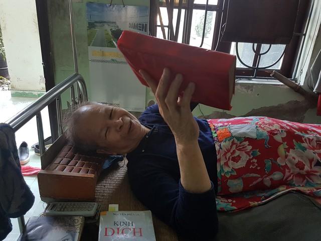 Cụ Nguyễn Văn Khuê nhoẻn miệng cười khi nói về những cuốn sách trên tay.