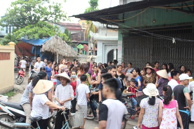 Người dân hiếu kỳ tập trung trước gia đình cháu Việt A. Ảnh: N.Hằng