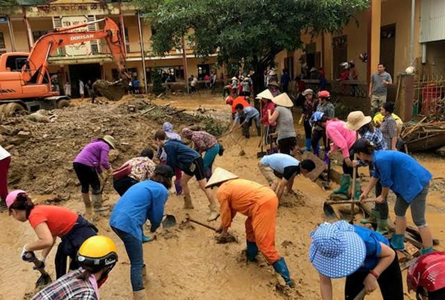 Cán bộ và người dân chung tay nỗ lực khắc phục hậu quả trận lũ.