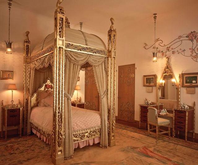 Một trong số 58 phòng ngủ có một chiếc giường cỡ lớn, với bốn chân giường bằng vàng và bộ bàn ghế trang điểm cùng phong cách.
