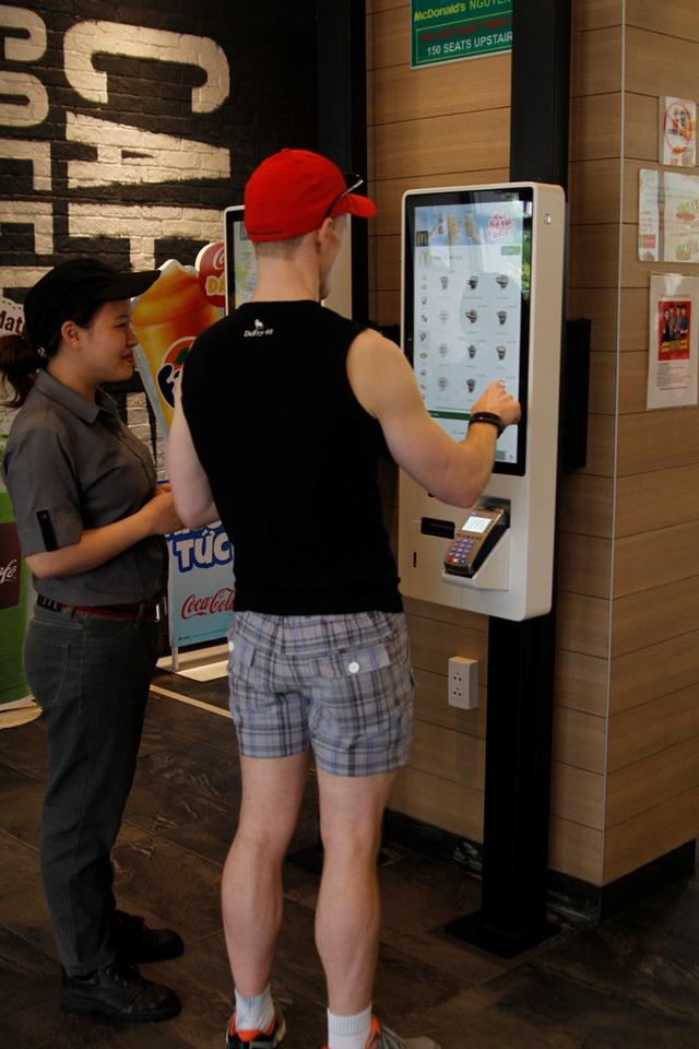 Khách hàng đặt món trên ki-ốt với sự hướng dẫn của nhân viên McDonald's