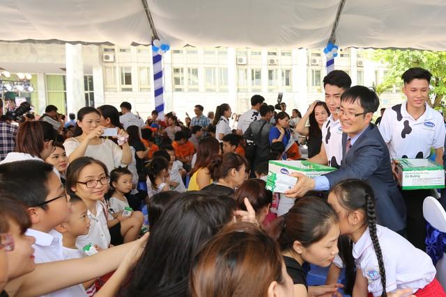 Ông Phan Minh Tiên – Giám đốc Điều Hành Vinamilk trao sữa cho các em nhỏ.