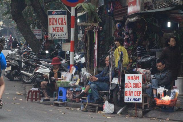 Vỉa hè ngoài là điểm để xe máy còn là nơi sửa chữa giầy dép, bán băng đĩa hành nghề.