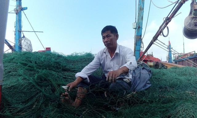 Ông Bùi Xuân Tấn sửa soạn lại ngư cụ bị hư hại. Ảnh: L.C