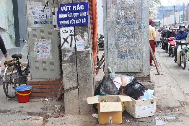 Rác thải được vứt ngay dưới biển cấm tại đường Cầu Giấy (quận Cầu Giấy).