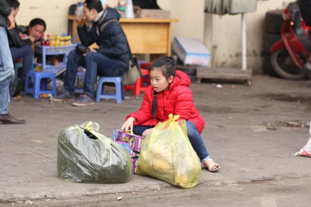 Một em bé ngồi thẩn thờ chờ người thân di chuyển đồ đạc.