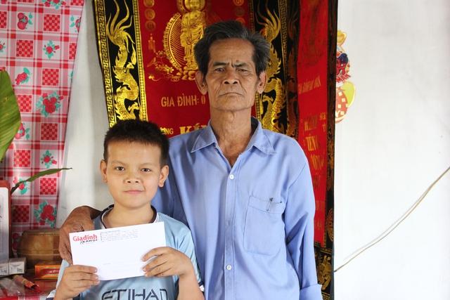Em Hiếu và ông ngoại của mình nhận quà giúp đỡ đợt đầu tiên từ đông đảo bạn đọc thông qua nhịp cầu Vòng tay Nhân ái. Ảnh: H.Phương