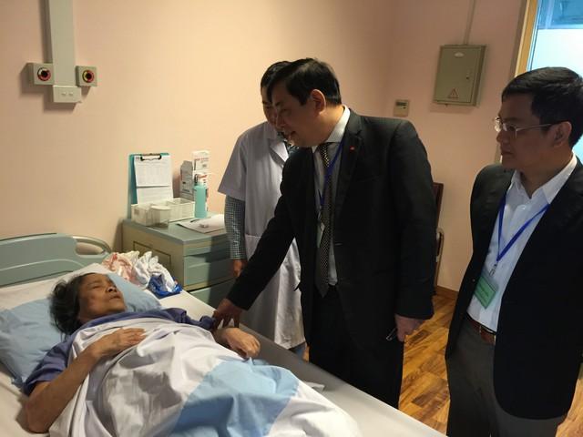 PGS.TS Lương Ngọc Khuê thăm hỏi tình hình sức khoẻ một bệnh nhân đang điều trị nội trú tại Bệnh viện Đại học Y Hà Nội.