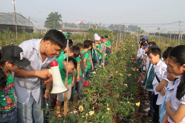 Học sinh vừa tham quan vừa học về cách chăm sóc các loại hoa tại vườn.