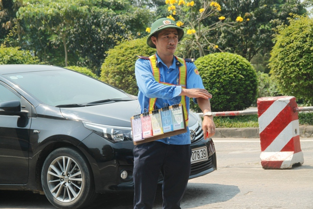 Dưới nắng gay gắt, một nhân viên trạm thu phí bán vé phía ngoài trạm.