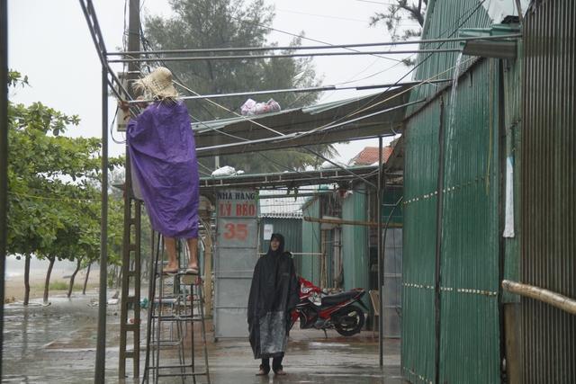 Các ki ốt kinh doanh dọc bãi biển Cửa Lò được người dân tháo bớt mái tôn, gia cố lại.