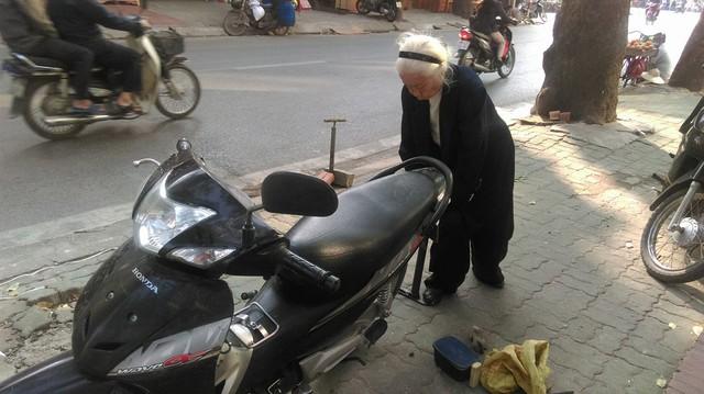Gần 90 tuổi, cụ Nguyễn Thị Vân vẫn nhanh nhẹn trong việc bơm, vá xe. Ảnh: Ngọc Thi