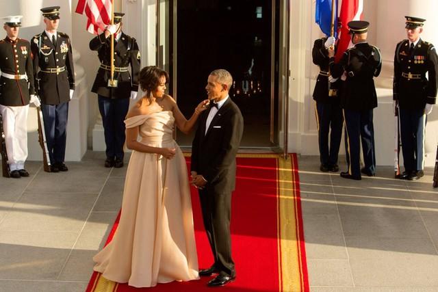 Sau hai nhiệm kỳ, câu chuyện tình yêu đẹp này vẫn thu hút sự quan tâm đặc biệt của báo giới, công chúng bởi những cử chỉ ân cần họ dành cho nhau như cách ông Obama cầm tay che ô cho vợ, hay bà Michelle chỉnh trang cho chồng mình trước ống kính. Ảnh: Time