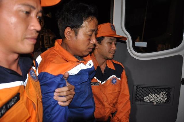 Thuyền trưởng Nguyễn Viết Thắng (người đi giữa) được dìu ra xe cấp cứu, sau khi về bờ . Ảnh: Tuổi trẻ