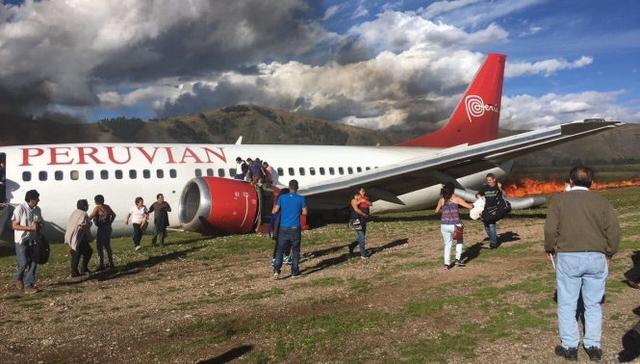 Hành khách đang được sơ tán khỏi máy bay bị cháy - Ảnh: RT/Twitter